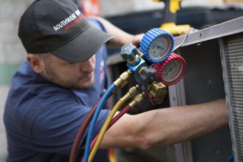 serwisant klimatyzacji podczas wykonywania pracy