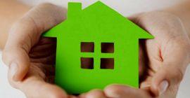 zielony domek trzymany w dłoniach